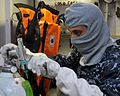 A Sailor checks an oxygen tank. (8455083699).jpg