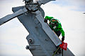 A Sailor fits a cover over a helicopter tail rotor. (9095478218).jpg