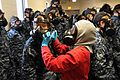A fire fighting instructor assists a recruit with how to properly seal her gas mask. (32441379906).jpg