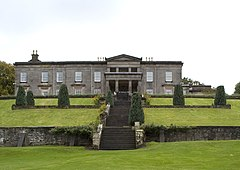 A photograph of the north face of Aberlour House, with a flight of stone steps leading to the house in the foreground