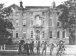 Addiscombe Military Seminary - East front of Addiscombe Place, the main building of Addiscombe Seminary, photographed in c.1859. Cadets pose in the foreground. The inscription Non faciam vitio culpave minorem can be seen on the entablature