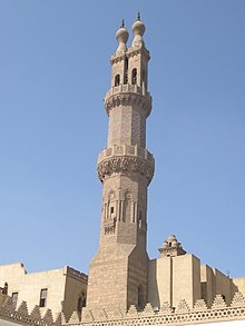An ornate carved stone octagonal minaret, with a carved stone railing around balconies at its center and near its top. Above the second balcony the minaret splits into two rectangular shafts, each tipped by railing and a bulb-shaped finial.