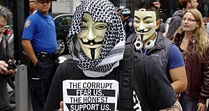 Anonymous (group) - A member holding an Anonymous flier at Occupy Wall Street, a protest that the group actively supported, September 17, 2011