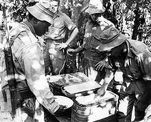 A soldier with his rifle slung is holding a plate and is being served food by another soldier while two others look on.