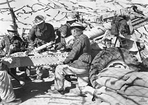 Five soldiers wearing steel helmets with a field gun. One is looking through a sight; one is loading a round; another is holding a round. The gun position is sandbagged and covered with camouflage netting.