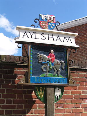 Aylsham - Aylsham town sign, typical of many Norfolk village signs, stands at the entrance to the town. It depicts John of Gaunt, Lord of the manor from 1372.