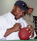 A picture of Bo Jackson signing a football.