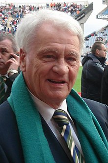 The head and shoulders of a white-haired gentleman in his 70s. He is wearing a white shirt, black jacket, white-green-and-blue striped tie, and a green scarf.