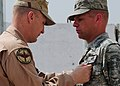 Brig. Gen. David Allvin, 438th Air Expeditionary Wing Commander, pins the Joint Service Commendation Medal with V on Capt. Michael Bradley at Kabul International Airport.jpg