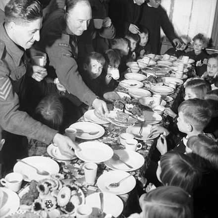 British soldiers serving food to Dutch children at a St Nicholas Day party in Holland, 7 December 1944. British soldiers serving food to Dutch children at a St Nicholas Day party in Holland, 7 December 1944. B12555.jpg