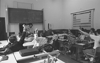 Students raising their hands to indicate they know the answer, Bonn, 1988 Bundesarchiv B 145 Bild-F079061-0003, Bonn, Gymnasium.jpg