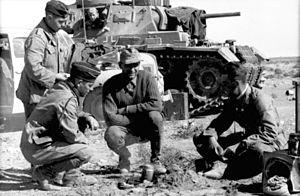 Afrika Korps - Panzer crew warms up a meal.