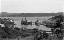 A large warship is tied to the dock in a narrow channel of water. Two smaller ships are alongside her.