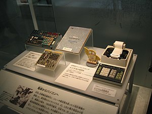 Busicom - On the left, the NEC TK 80 kit, based on Intel 8080 chip, on the centre, Busicom calculator motherboard, based on Intel 4004 chip, and on the right, the Busicom calculator, fully assembled in Ueno, Tokyo