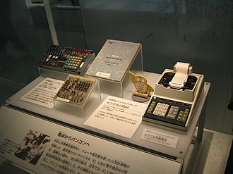 Busicom - On the left, the NEC TK-80 kit, based on Intel 8080 chip, on the centre, Busicom calculator motherboard, based on Intel 4004 chip, and on the right, the Busicom calculator, fully assembled in Ueno, Tokyo