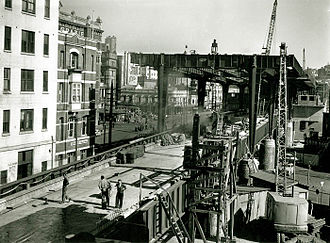 Circular Quay railway station - Circular Quay railway station and the Cahill Expressway under construction in 1955. Workmen can be seen standing on the viaduct leading into and through the station, which was completed the previous year in 1954.