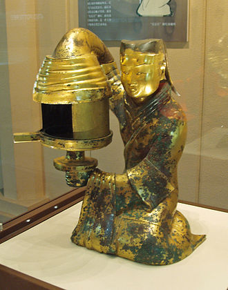 Han dynasty - A gilded bronze oil lamp in the shape of a kneeling female servant, dated 2nd century BC, found in the tomb of Dou Wan, wife of the Han prince Liu Sheng; its sliding shutter allows for adjustments in the direction and brightness in light while it also traps smoke within the body.