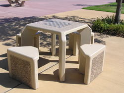 A chess table is a table with a chessboard painted or engraved on it. The photograph shows a chess table in a park.