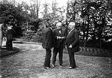 Drie mannen in pakken wisselen elkaar af in een park, met twee individuen op de achtergrond