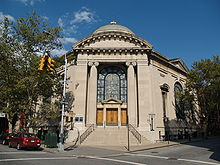 The front entrance of a hexagonal building capped by a dome is visible, facing a street-corner. The entranceway is framed by large stone columns and flanked by metal seven branched menorahs on each side. There are four wooden doors, one on each side and two in the middle, topped by a large arched stained-glass window. A stone stairway with metal railings on each side leads up from the sidewalk to the doors.