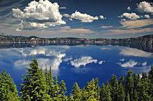 Flat, blue lake clearly reflecting a cloudy sky, fronted by pine forest