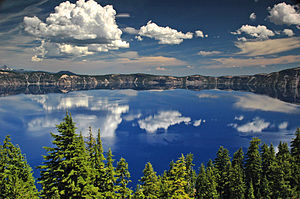 Photograph of Crater Lake depicting clear blue waters reflecting fluffy clouds with forestry peeking out in the forefront