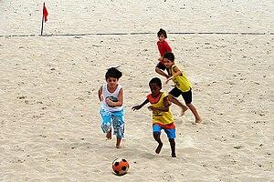 Português: Crianças jogando futebol de areia e...