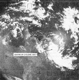 Satellite image of a small tropical cyclone near the northeastern coast of Australia. A long band of clouds is seen extending to the southeast.