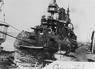 Russian battleship Tsesarevich - A stern view of Tsesarevich dockside at Port Arthur, 1904. Shrapnel holes are visible in her funnels.