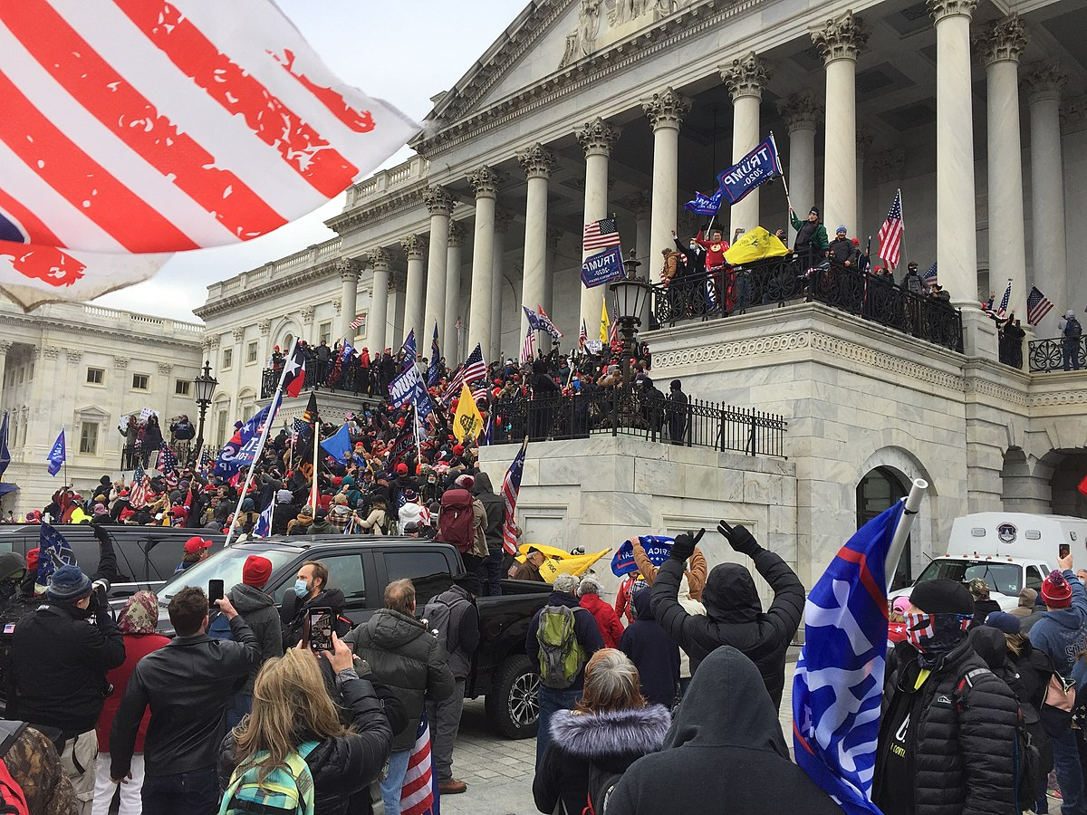 A photo of the Capitol Hill Insurrection Attempt on January 6, 2021. It's the outside of the government building with a huge crowd of people standing on the steps. This appears to be before people began breaking into the building, intent on murdering congresspeople.