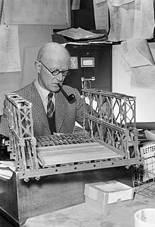 A middle-aged man sits at a desk while smoking a pipe; he is examining a model bridge in front of him