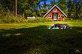 Dog in front of red swedish cottage, Fjärdlång, Stockholm (Sweden) - panoramio.jpg