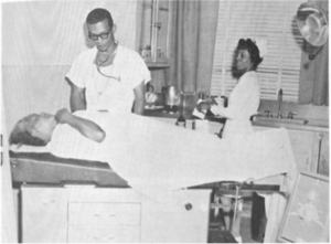 Dr. Moore, Obstetrician-Gynecologist, examining a patient, undated.