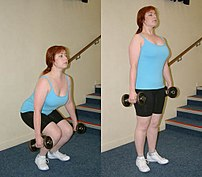 An individual performing a dumbbell squat.