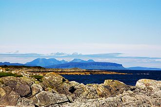 Small Isles - A distant view of Eigg, with the hills of Rùm behind
