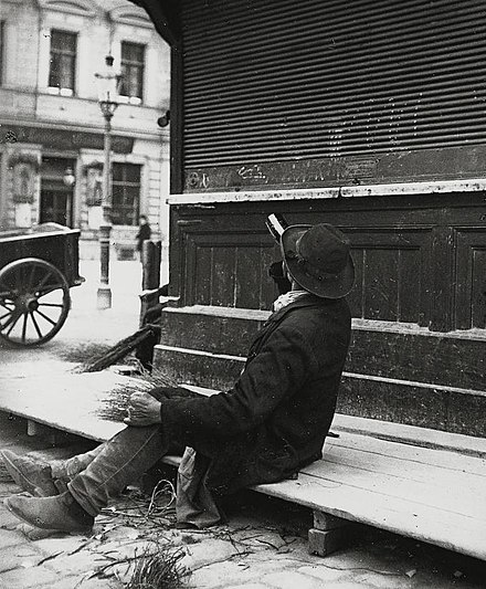 A man drinking from a bottle of liquor while sitting on a boardwalk, ca. 1905-1914. Picture by Austrian photographer Emil Mayer. Emil Mayer 024.jpg