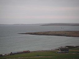 Holm of Houton offshore of Orkney Mainland, with Cava and Flotta beyond the ferry.