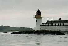 A small white lighthouse with a black canopy sits on a dark rock. There is a high white wall and a row of black and white houses to the right and dark hills at left in the distance.