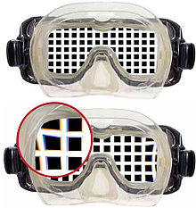 View of a rectangular grating through a flat-glazed diving half-mask, showing magnification and a detail of slight pincushion distortion and chromatic aberration in the through-water view.