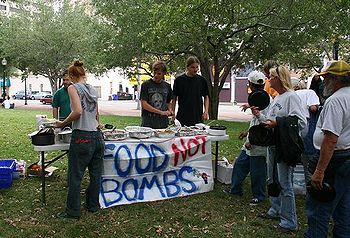 A Food Not Bombs chapter serves a meal in a public park.
