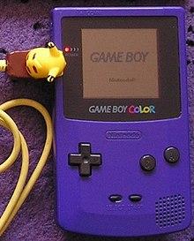 Photo d'une Game Boy mauve avec un câble link jaune en forme de Pikachu.