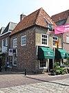 foto van Huis op de hoek van de Hoofschestraat, met overstekend schilddak, waarin een hijsluik, grijsgepleisterde voorgevel. Onbewoonbaar verklaard