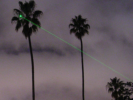A 5 mW green laser pointer directed at a palm tree at night. Note that the beam itself is visible through Rayleigh scattering. Green-lased palm tree (crop).jpg
