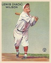 A man wearing a white baseball uniform and cap with red trim swinging a baseball bat