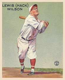 A baseball card image of a man wearing a white baseball uniform and cap with red trim swinging a baseball bat