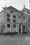 foto van Herenhuis op de hoek van de schoolstraat, met gebosseerd grijsgepleisterde lijstgevel, schilddak en ingang met kroonlijst op voluutvormige consoles uit plm 1830-50