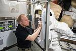 ISS-47 Tim Kopra prepares a spacesuit in the Quest airlock.jpg