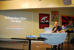 Jamyang Norbu - Independent Tibet Presentation by Jamyang Norbu, New York City, 20 August 2011. Behind presenter is a photo of The 14th Dalai Lama, Students for a Free Tibet (SFT) logo and the Tibetan Flag.