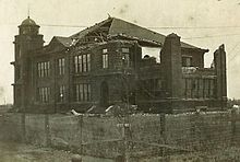 Old photo of a building that has part of its facade damaged.