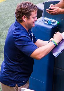 Candid waist-up photograph of Schneider wearing a blue shirt and signing an autograph.